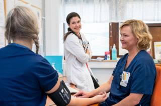 Hoitaja mittaa toiselta hoitajalta verenpainetta terveyskeskuksen tiloissa, lääkäri seisoo taustalla.