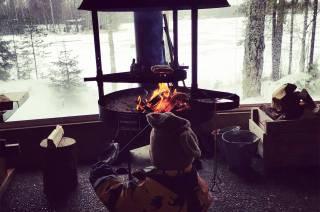 Poika paistaa makkaraa Pappilanniemen luontopolun kodassa.