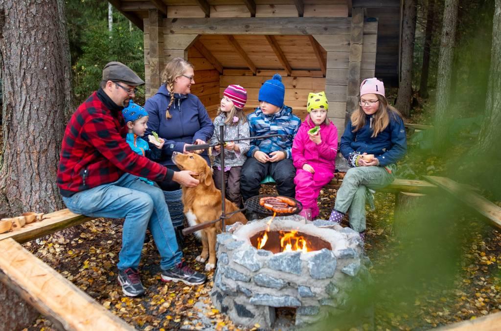Perhe grillaa makkaraa laavun edustalla