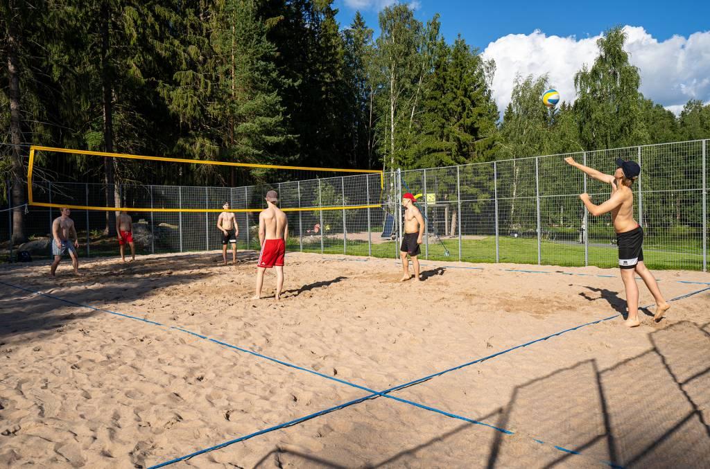 Miehet pelaavat beach volleyta kesällä.