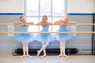 kolme balettitanssijaa seisovat hymyillen ikkunan vieressä.