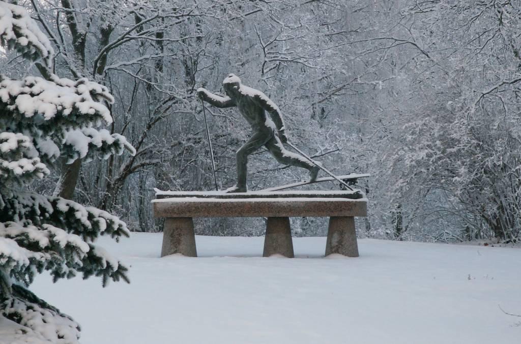 Hiihtäjä-patsas talvella lumisessa maisemassa Lepänkorvan puistossa Valkeakoskella.