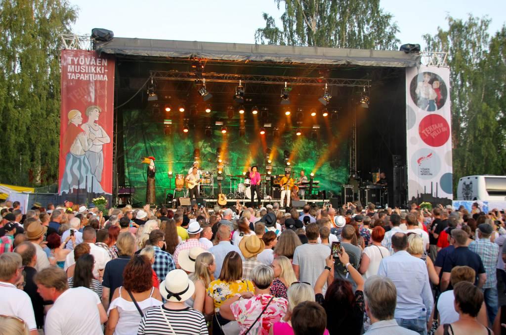 Tapahtumalavalla esiintyjiä ja lavan edessä yleisöä Työväen Musiikkitapahtumassa.