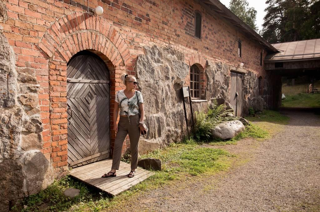 Nainen seisoo Voipaalan alueen vanhan tallin edessä.