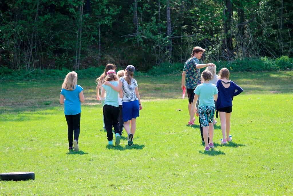 Ryhmä lapsia kävelee nurmikolla.