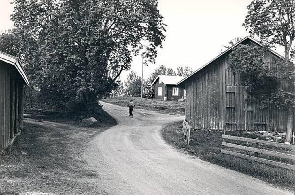 Poika pyöräilee Huittulanharjulla mustavalkoisessa vanhassa kuvassa.