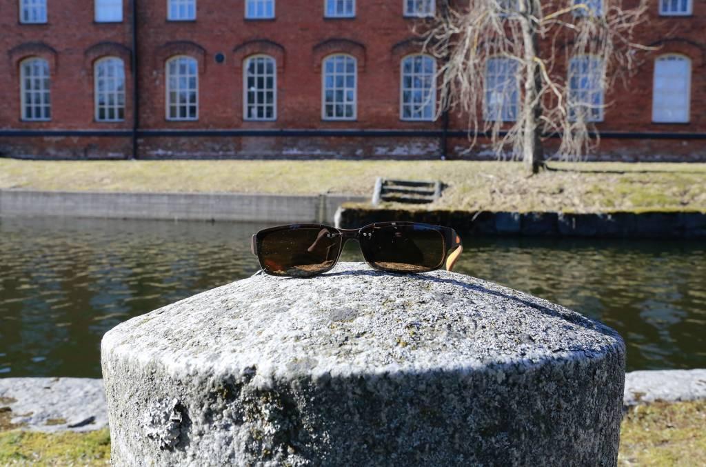 Aurinkolasit aseteltuna kiven_päällä kanavanrannassa.