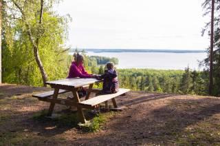 Nainen ja tyttö istuvat pöydän ääressä ja katsevat maisemia Rapolanharjulla.