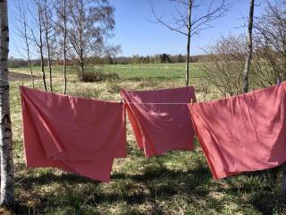 Punaisia lakanoita ulkona pyykkinarulla.