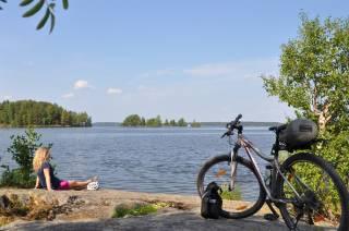 Nainen istuu kalliolla ja katselee Vanajavedelle, naisen pyörä on lisäksi kalliolla.