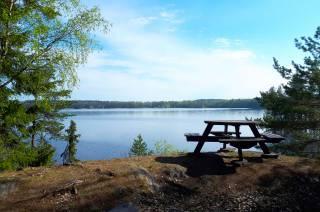Levähdyspaikka Pappilanniemen luontopolulla kallionpäällä Vanajaveden rantamaisemassa.