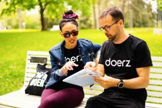 Nainen ja mies istuu puistonpenkillä tutkien karttaa.