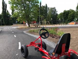 Punainen polkuauto ja taustalla leikkapaikka liikennepuistossa