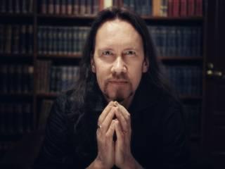Kirjailija JP Koskinen. Pitkät tummat hiukset ja parta.