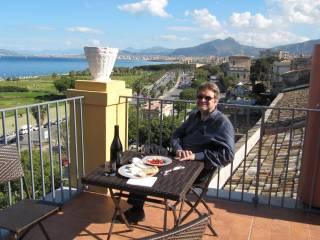 Kirjailija, säveltäjä Eero Hämeenniemi istuu parvekkeella Italian maisemissa.