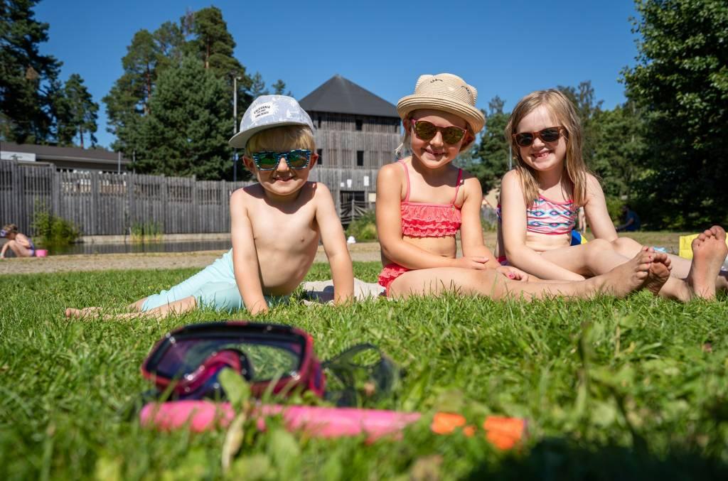 Lapset istuvat Apian uimarannalla nurmikolla ja taustalla näkyy Seikkailupuiston torni.