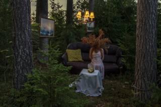 Nainen istuu metsässä sohvalla.