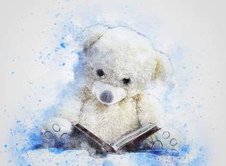 Valkoinen nalle lukee kirjaa.